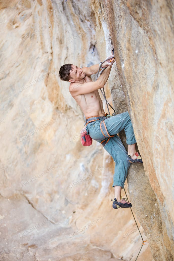 Rock climber clipping rope while climbing challenging route