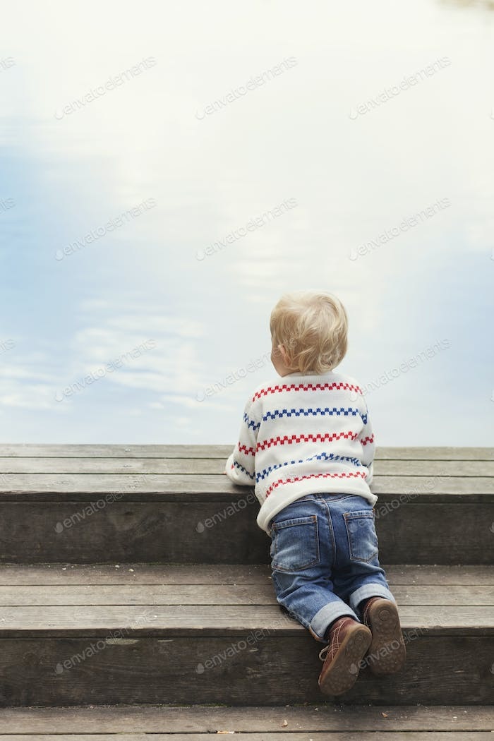 Rear view of baby girl on wooden steps against sky
