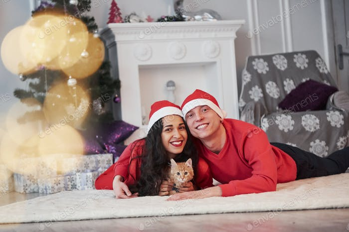 Portrait of couple with little kitty celebrates holidays in new year clothes
