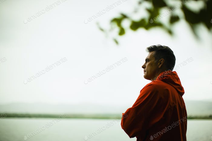 A middle aged man in a red jacket looking over water, deep in thought.