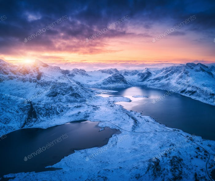 Aerial view of snowy mountains, sea, colorful sky at sunset