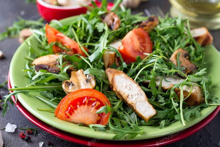 Close-up on a salad with chicken and tomato on green ceramic plate in a stone table. Healthy diet