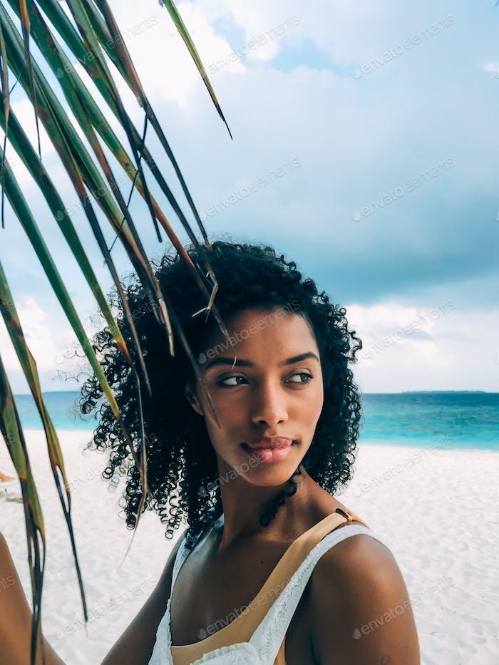 Frau auf den Malediven Insel Strand mit einem Palmenblatt