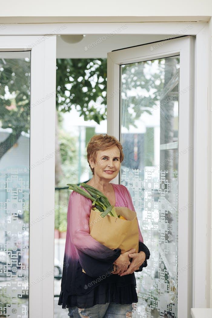 Senior woman entering house