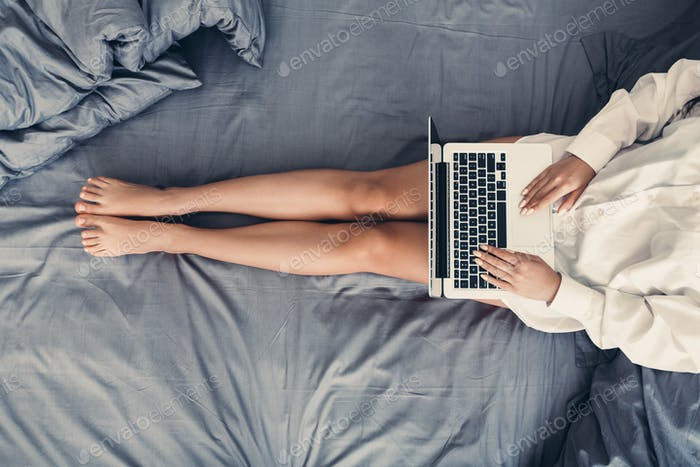 Woman using laptop, relaxing in her bed