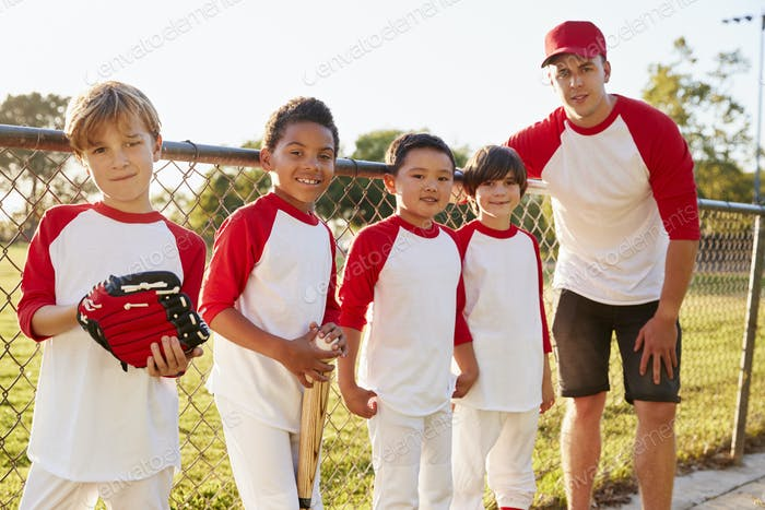 Coach and young boys in a baseball team looking to camera
