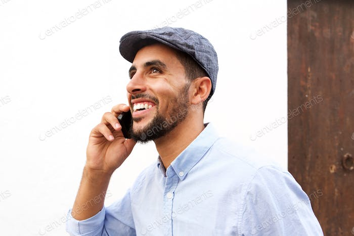 Close up happy young arabic man talking on mobile phone