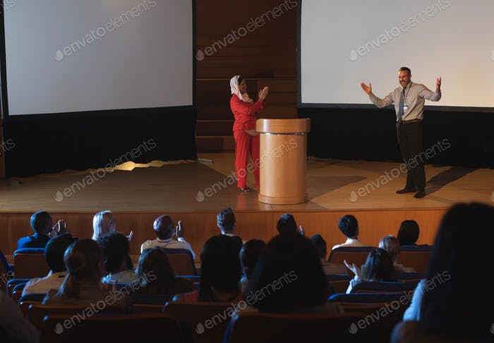 Happy businessman showing his presentation on stage in the auditorium while audience clapping hand