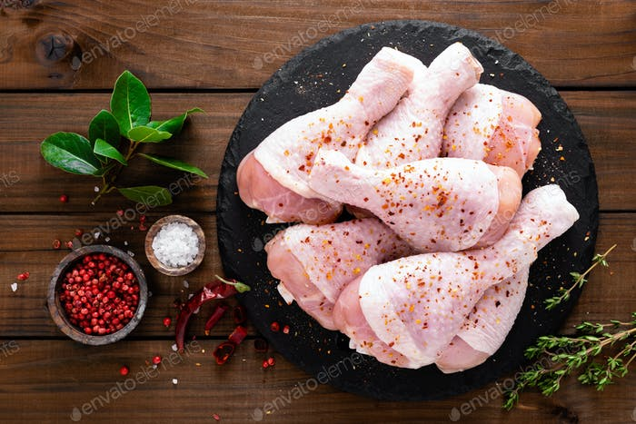 Raw fresh chicken legs on wooden background. Top view