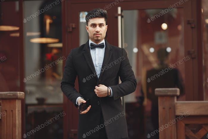 Stylish businessman in a black suit standing outside