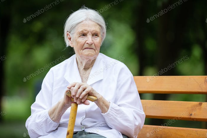 Senior woman sitting on bench in summer park