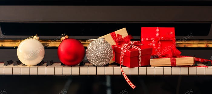 Chritmas balls and gift boxes on piano keyboard, front view