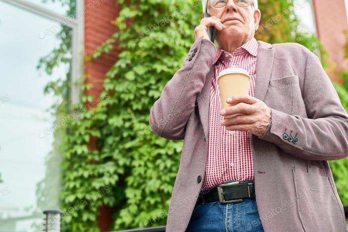 Moderner Senior Man spricht per Telefon im Freien