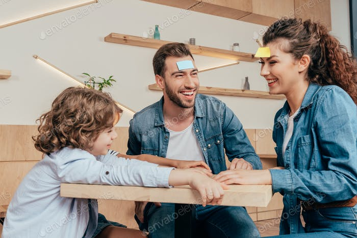 happy young family playing guess sticker