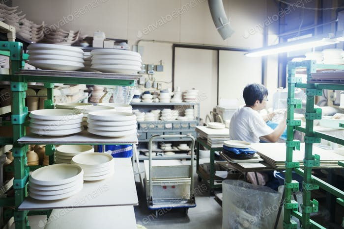 Man sitting in a Japanese porcelain workshop surrounded by shelves with white porcelain plates