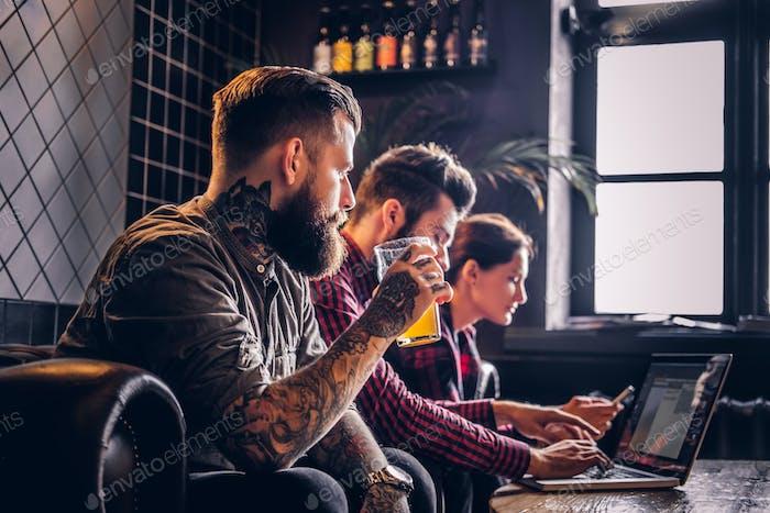 Группа студентов сидит на диване отдыхает в кафе и работает с ноутбуком по общему проекту.