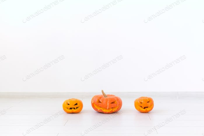 Jack-o-lantern carved pumpkin on light wall background with copy space, autumn and halloween home