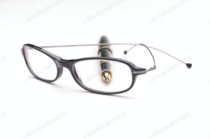 Glasses and pen on a white background