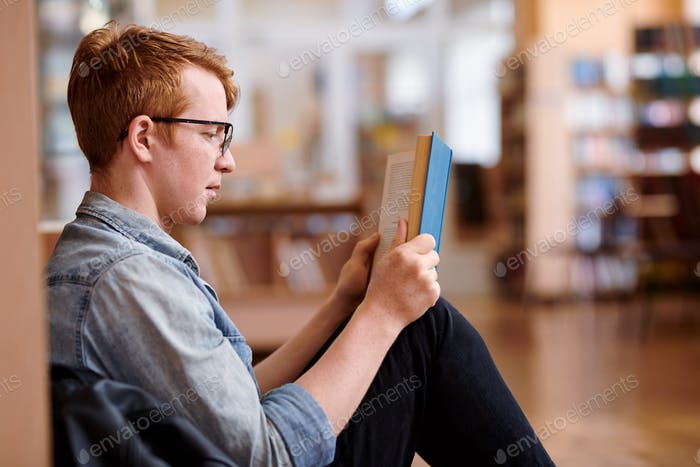 Young reader in casualwear reading by bookshelf in library