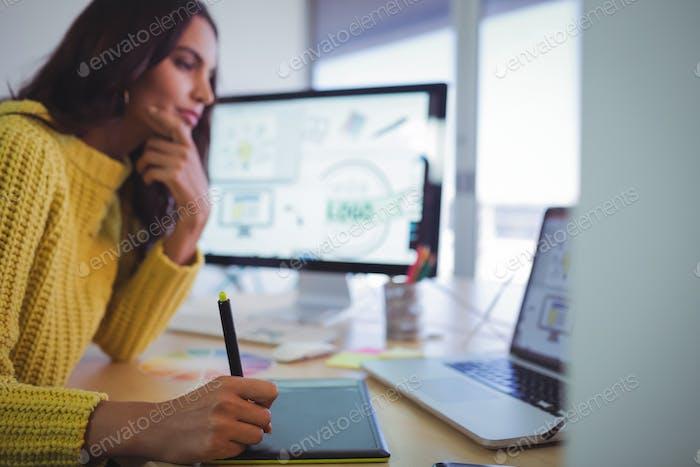 Female graphic designer using digitizer in office
