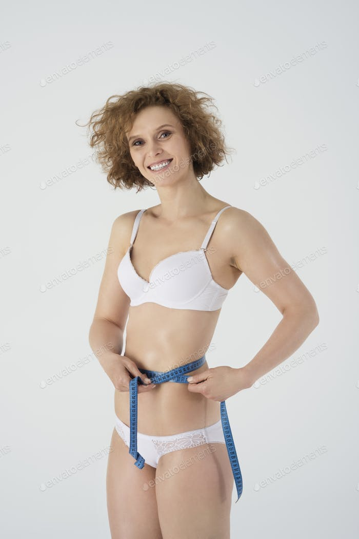 Woman measuring her thin waist
