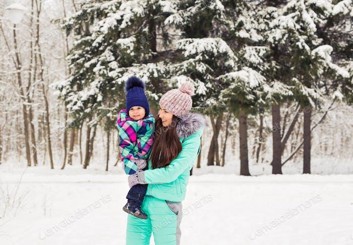 glückliche Mutter hält Baby Mädchen auf dem Spaziergang im Winter verschneiten Wald