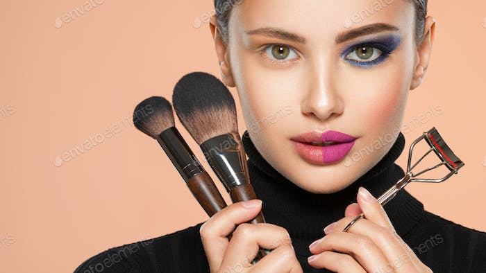 Portrait of a girl with  tools for making makeup near face.
