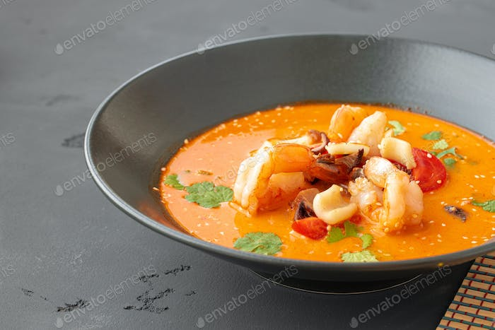 Tom Yam Thai soup in black bowl on gray table