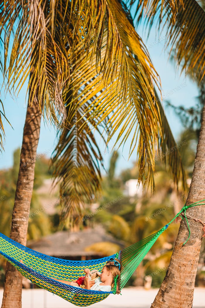Young man with laptop at hammock on tropical vacation