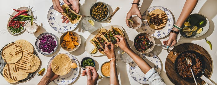 Family or friends having Mexican style Taco dinner with beer