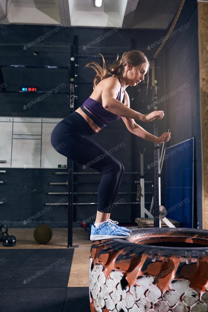 Woman Jumping on Tire in CrossFit Gym