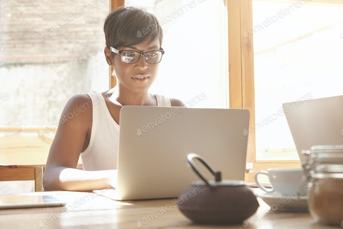 Young female freelancer working on laptop in cosy caf�Good-looking dark-skinned woman with short hai