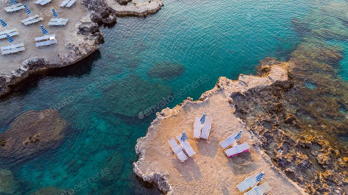 Chairs on Beach by Turquoise Water on Greek Island, Drone View