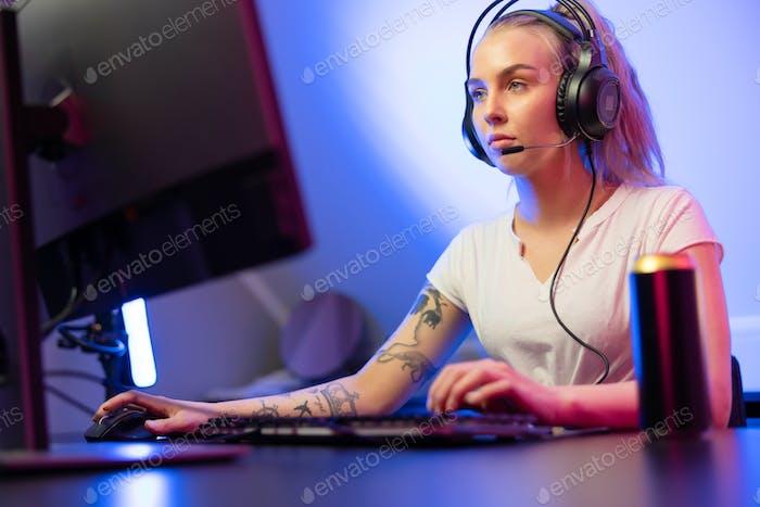 Professionelle Gamer Mädchen mit Headset spielen Online-Multiplayer-Video spiel auf dem PC