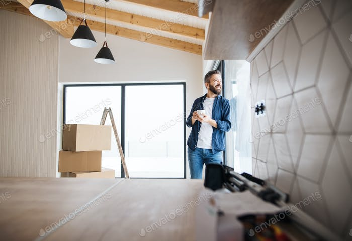 A mature man with cardboard boxes standing by a window, furnishing new house.