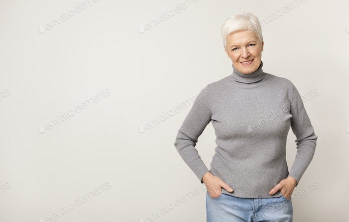 Portrait of beautiful aged woman on light studio background