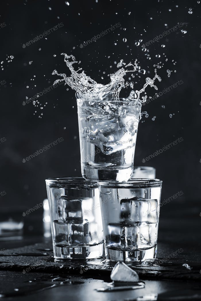 Vodka splash with spray from shot glasses on black stone background, iced strong drink