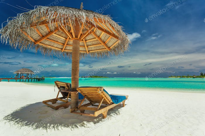 Two chairs and umbrella on stunning tropical beach, Maldives