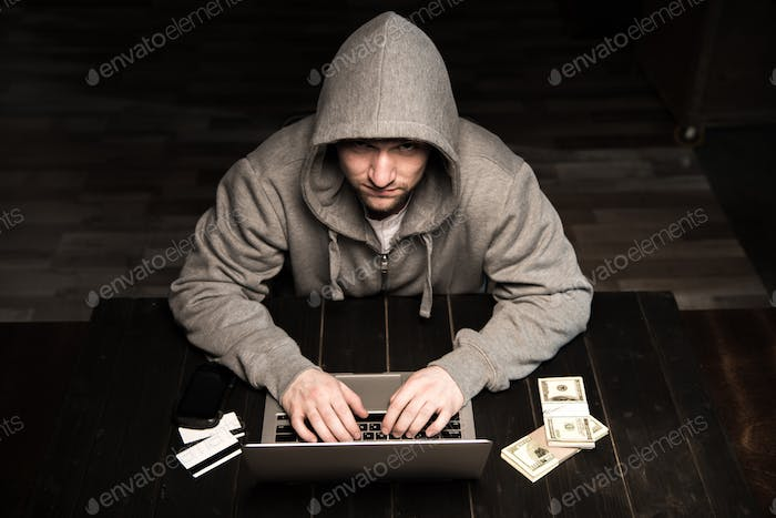 Young hacker in hoodie sitting at table and using laptop