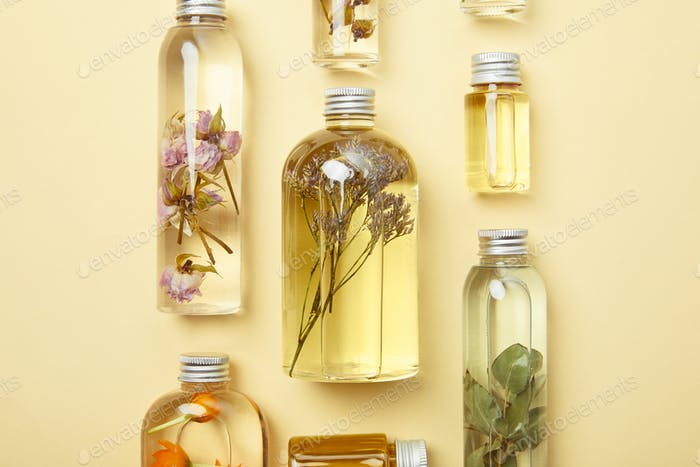 top view of transparent bottles with natural beauty products and dried wildflowers on yellow