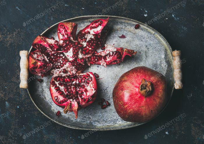 Fresh ripe pomegranate broken in metal tray over plywood background