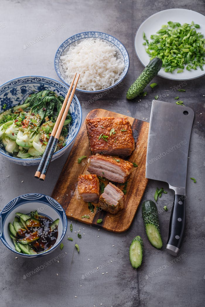 Crispy skin pork belly with salad and cucumbers