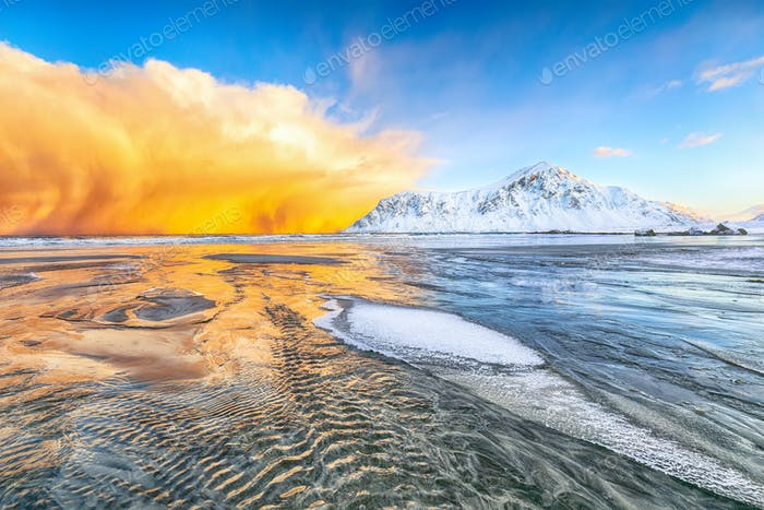 Fabulous winter scenery on Skagsanden beach with illuminated clouds during sunrise.