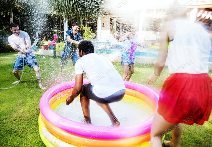 Diverse young adult splashing water in backyard