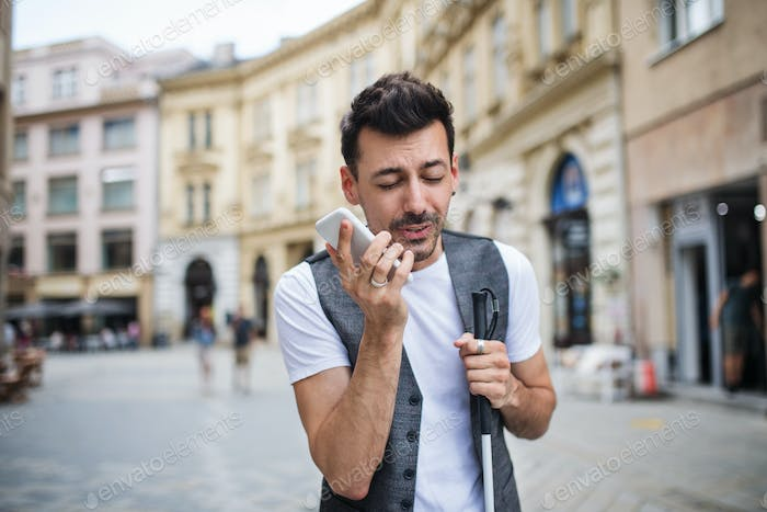 Young blind man with smartphone on street in city, making phone call.
