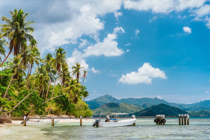Beautiful tropical scenery beach with palm trees, jetty pier, tourist boat and white clouds above