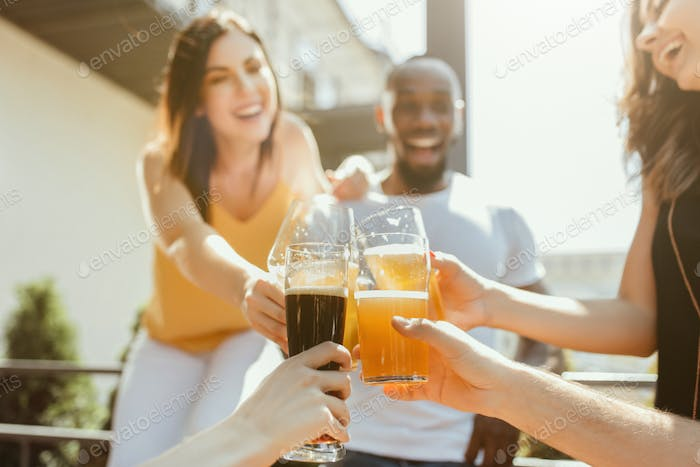 Young group of friends drinking beer and celebrating together