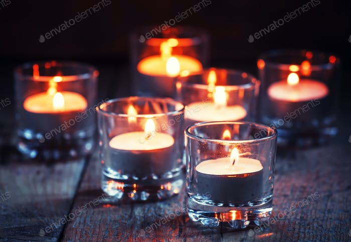 Burning small candles in glass candlesticks, Christmas or New Year's decoration
