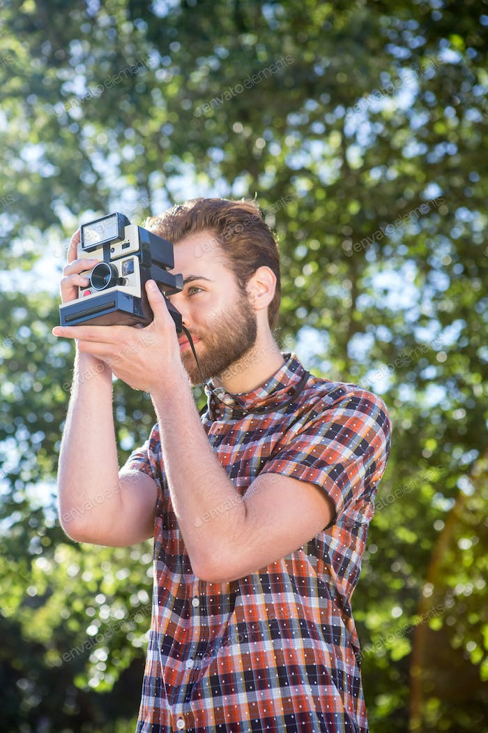 Handsome hipster using vintage camera on a summers day