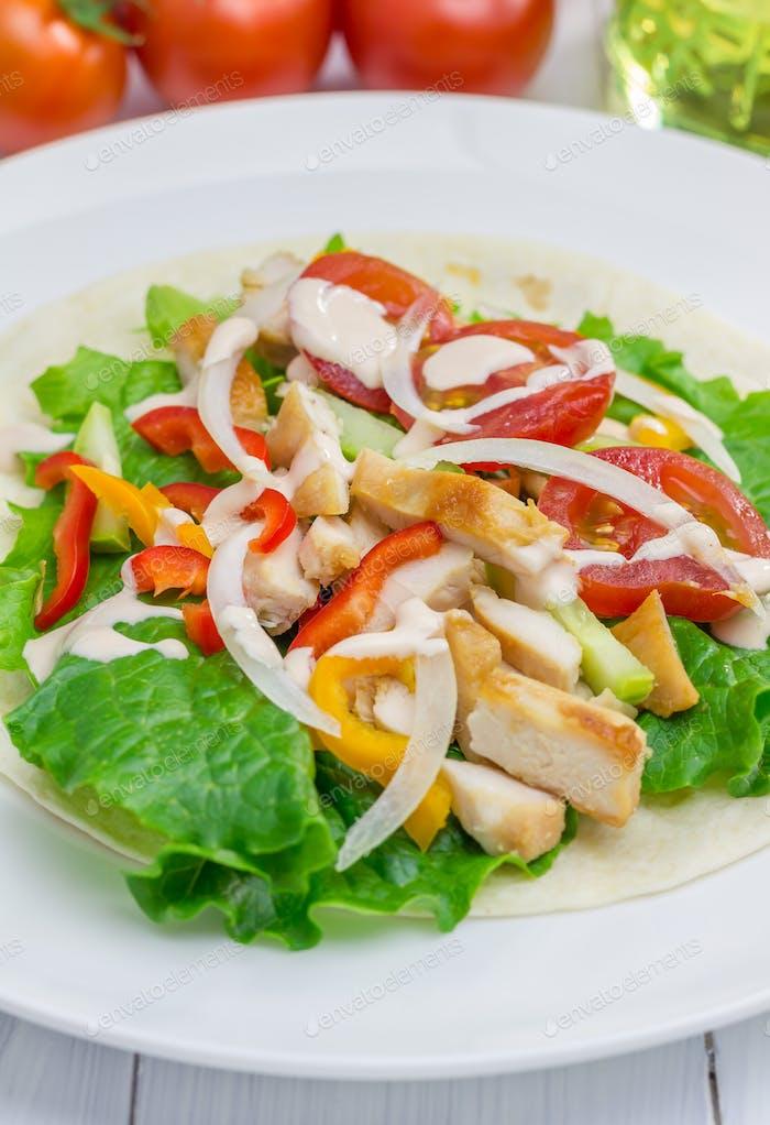 Gebratenes Hähnchenfilet auf Weizentortilla mit Salat aus frischem Gemüse